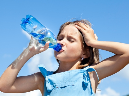 Attractive young beautiful girl drinking water from plastic bottles