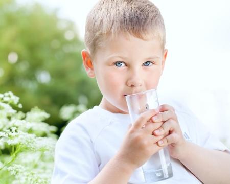 manos limpias: Niño que bebe el agua pura en la naturaleza