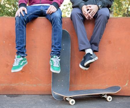 boy skater: Two friends skateboarders in the skatepark rest after skating Stock Photo