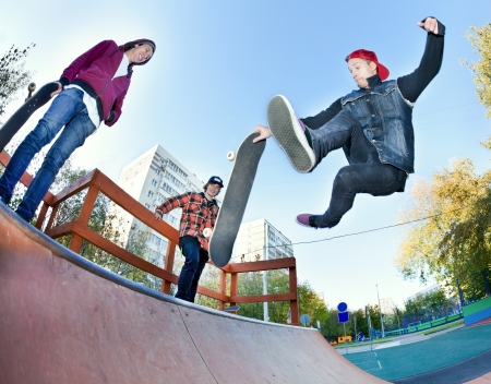 halfpipe: Skateboarder with friends in the skatepark jumping in the halfpipe