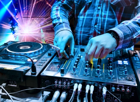 Dj mixes the track with a cigarette in his hand in the nightclub at a party. In the background laser light show photo