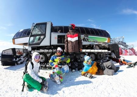snowcat: Friends snowboarding on a mountain top about snowcat