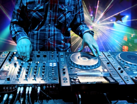 dj: Dj mixes the track in the nightclub at a party  In the background laser light show