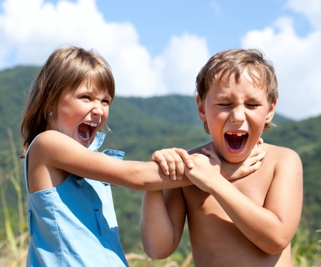 Angry boy and a girl scream and fight with each other outdoors photo