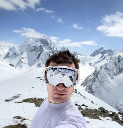 Blue Ridge Mountains: Portrait of snowboarder in the protective mask. Beautiful mountain landscape of the Caucasus Mountains Dombai