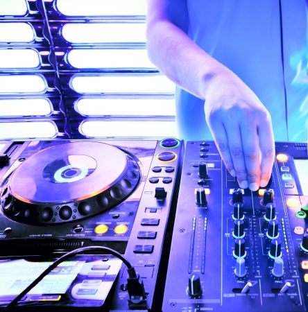 club scene: Dj playing the track in the nightclub at a party