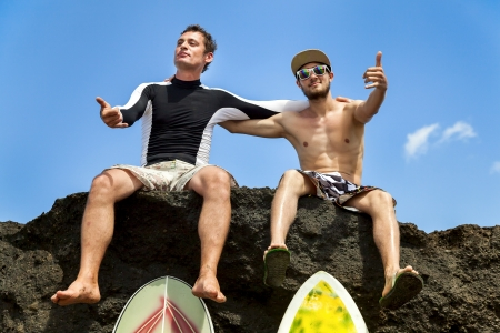 Two friend surfer sitting on a rock showing sign OK