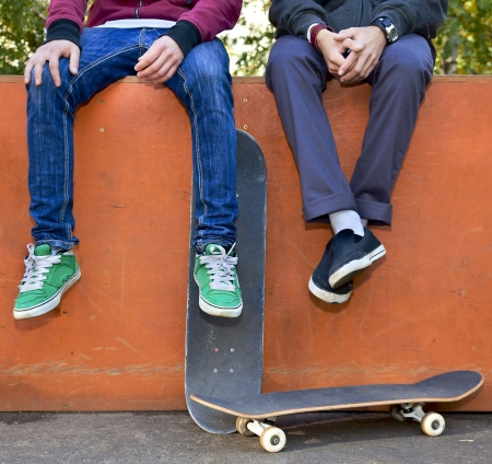 skateboard shoes: Two friends skateboarders in the skatepark rest after skating Stock Photo