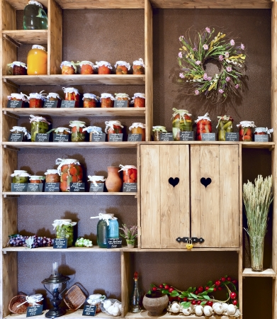 Domestic stocks with pickled vegetables in glass jars on wooden shelves photo