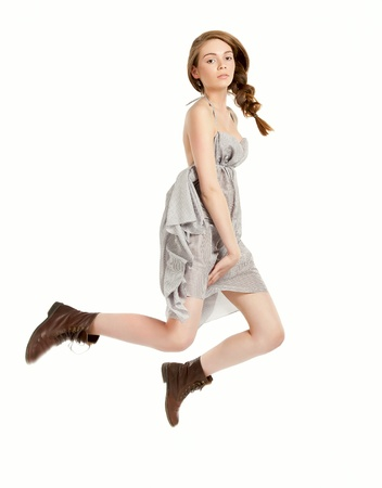 dynamic activity: Young beautiful girl doing jumping in studio on white background