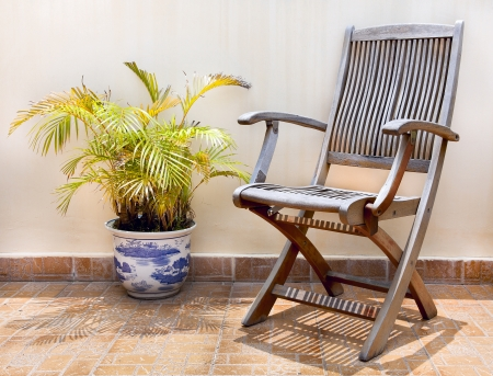 Stone terrace in the courtyard with wooden chair and palm tree in pot photo