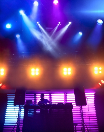 DJ mixes track at nightclub on scene. Bright beautiful lighting photo