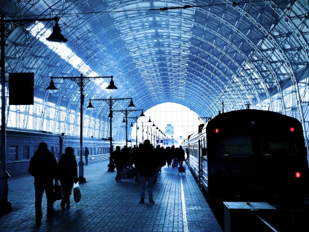Covered railway station with trains and silhouettes of hurrying people photo