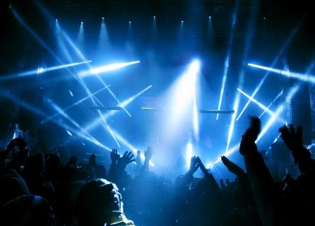 speaker: Siluetas de la gente y los m�sicos en el escenario gran concierto. Hermosos rayos de luz brillante