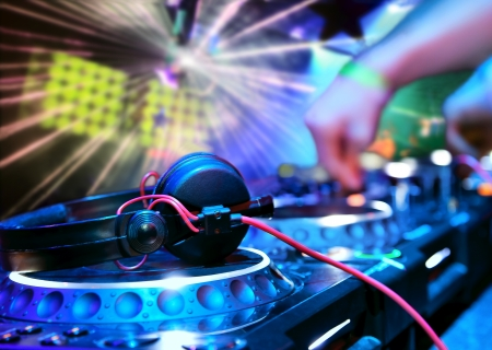 discotheque: Dj playing the track in the nightclub at a party. DJ headphones