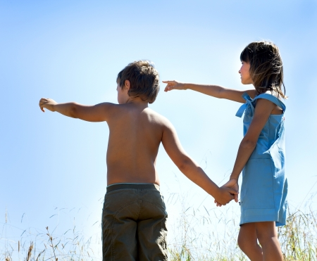 outstretched arms: Boy and girl holding hands on blue sky background Stock Photo