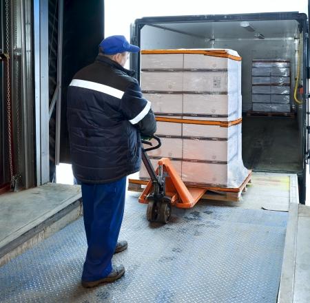 Worker loading truck on forklift Standard-Bild