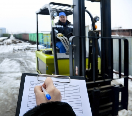 Forklift stands at the entrance to warehouse and hand of woman makes a record delivery of goods