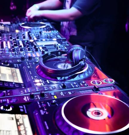 party dj: DJ tocando la pista en la discoteca en una fiesta