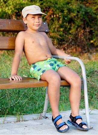 sandalias: Niño pequeño sonriente y sentado en el banco en el parque Foto de archivo