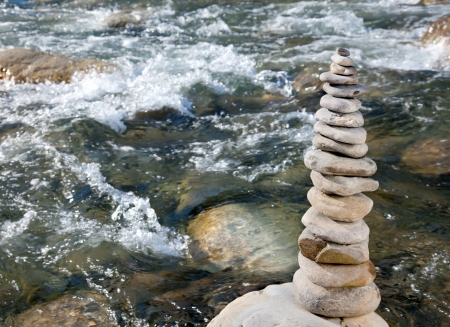 rock layers: Pyramid of stones beside a mountain river Stock Photo