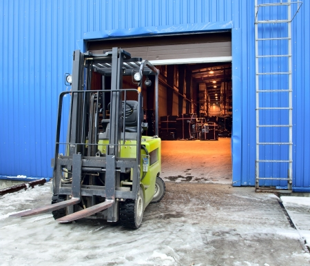 Forklift standing at the entrance of a large modern warehouse photo