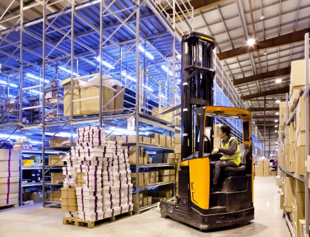 Werknemer in de beweging op heftruck in de grote moderne warehouse