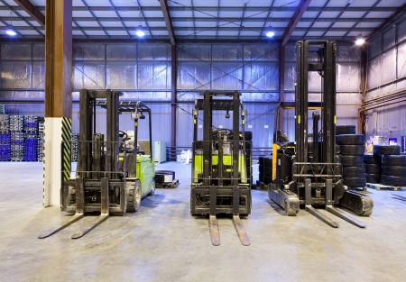 forklift driver: Three forklift in the large modern warehouse