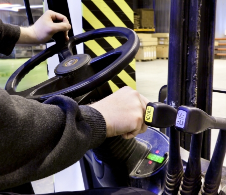 forklift driver: Hands of the driver of a forklift in warehouse  Stock Photo