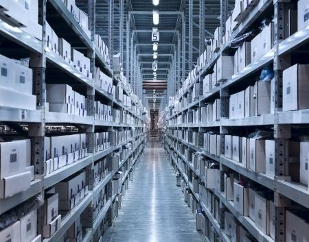 iluminacion: Interior del nuevo y moderno espacio de almacén en una gran sala bien iluminada. Las filas de estantes con cajas Foto de archivo