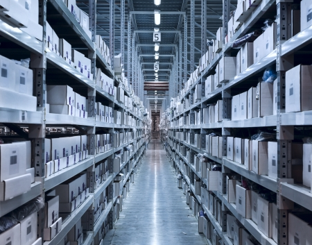 supplies: Interior of the new and modern warehouse space in a well lit large room. Rows of shelves with boxes Stock Photo