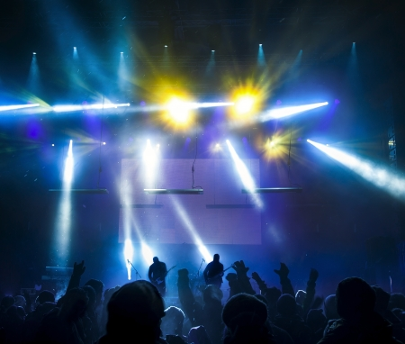 club scene: Silhouettes of people and musicians in big concert stage. Bright beautiful rays of light