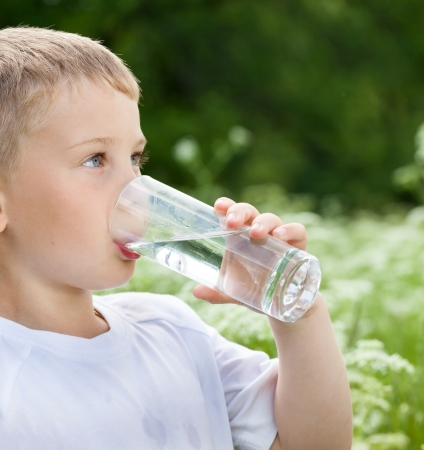tomando agua: Ni�o que bebe el agua pura en la naturaleza