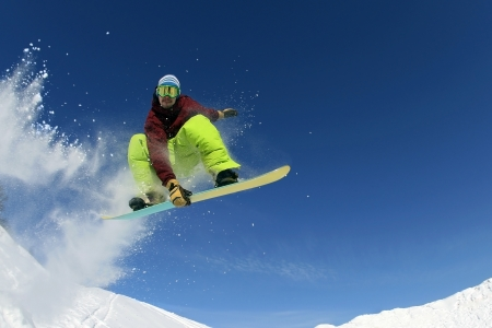 snowboard: Jumping snowboarder keeps one hand on the snowboard on blue sky background Stock Photo