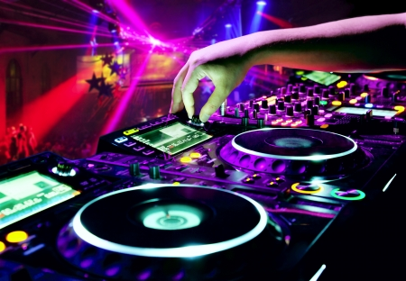 audio mixer: Dj mixes the track in nightclub at party