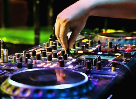 mezclador: DJ mezcla la pista en el club nocturno en una fiesta
