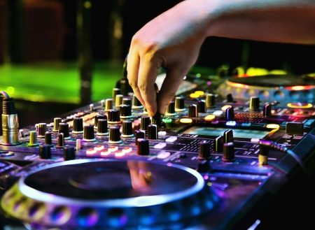dj: Dj mixes the track in the nightclub at a party