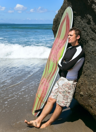 wetsuit: Thoughtful tanned surfer on the ocean with board
