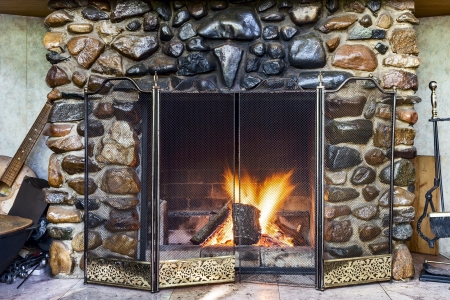 stone  fireplace: Stone fireplace in country house and fire blazing inside with natural light Stock Photo