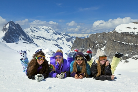 girl in sportswear: Four smiling young girls are snowboarders on the snow in mountains in French Alps