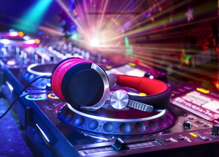 audio mixer: Dj mixer with headphones at nightclub.  In the background laser light show Stock Photo