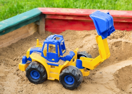 Children's toy tractor in sandbox photo