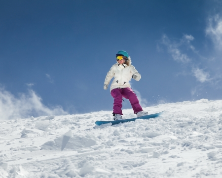 snowy mountain: Young girl snowboarder in motion on snowboard in mountains