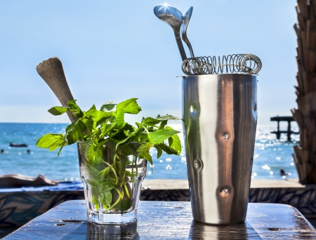 inox: Bar accessories with inox shaker, mint in a glass on the Sea Stock Photo