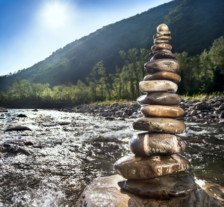 Pyramid of stones beside a mountain river Stock Photo