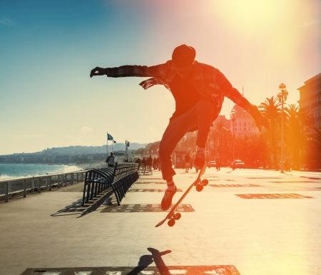 Silhouette of Skateboarder jumping in city on background of promenade and sea Stock Photo