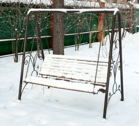 Bench swing covered in snow photo