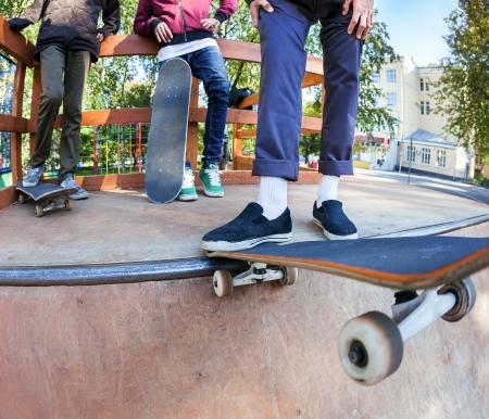 Three friends skateboarders in halfpipe skatepark