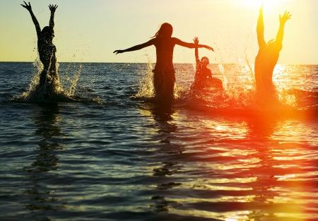Silhouetten van jonge groep mensen springen in zee bij zonsondergang