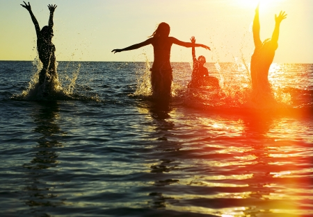 guy on beach: Silhouettes of young group of people jumping in ocean at sunset
